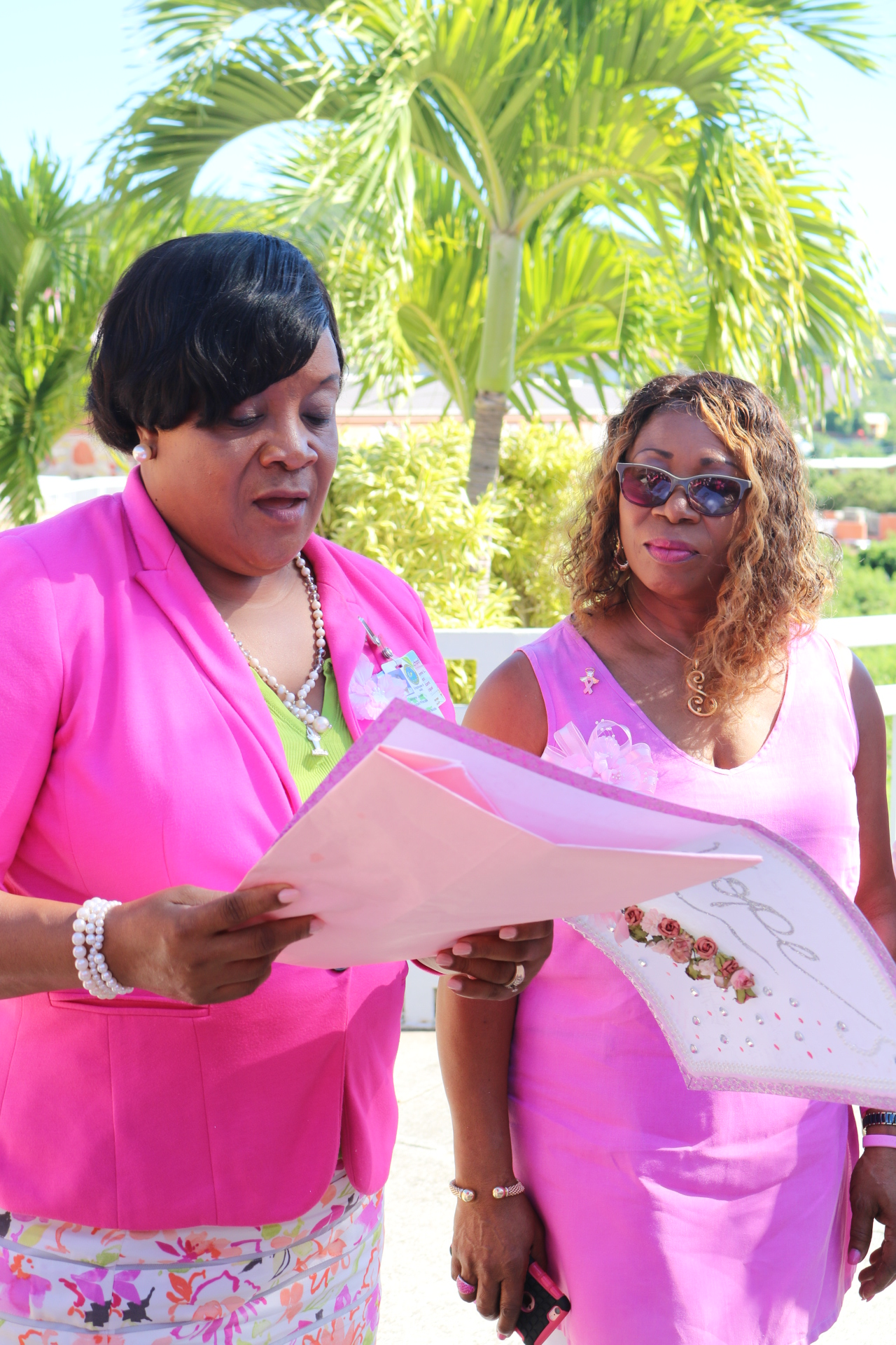 Assistant Principal Dr. Merlene Jones reads card aloud to breast cancer survivor Margarita Charles-Smith.jpeg