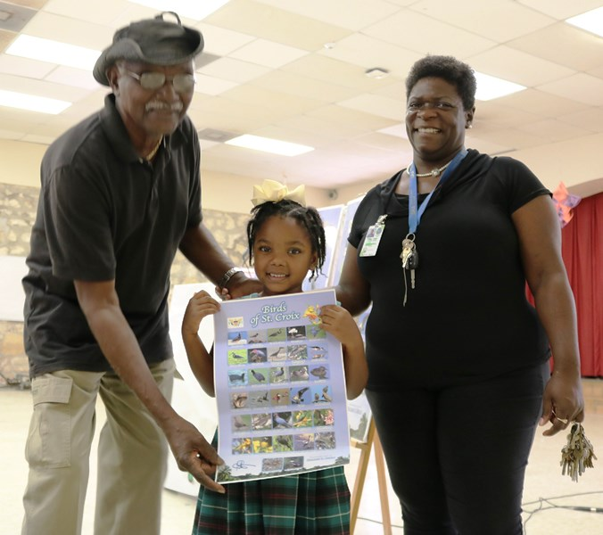Peters donates bird poster to student.jpg